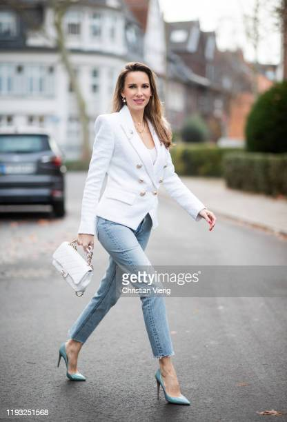 Alexandra Lapp is seen wearing white double-breasted Balmain blazer with golden buttons, silk top, white Chanel bag, light blue ripped Celine denim...