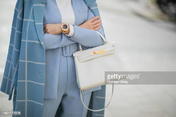Alexandra Lapp is seen wearing ZARA oversized checked coat in light blue, ZARA blazer in pastel blue, ZARA knit jumper in white, ZARA pants in pastel...