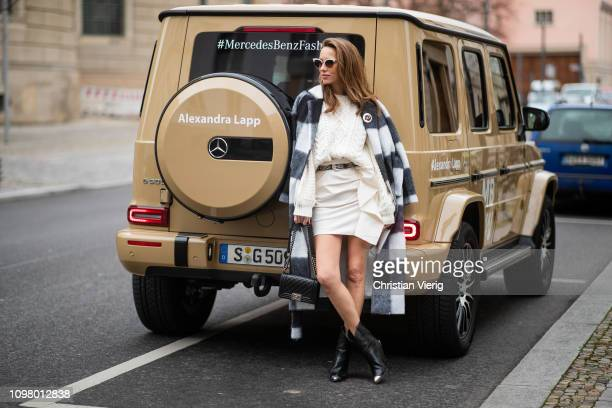 Alexandra Lapp is seen with Mercedes G500 wearing a black and white checked woolblend coat from Ganni offwhite cable knit sweater from Maje Isabel...