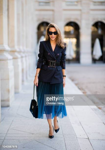 Alexandra Lapp is wearing pleated skirt navy striped blazer with belt and bag all Marc Cain heels is seen during Paris Fashion Week Womenswear...