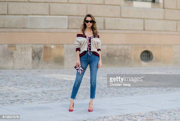 Alexandra Lapp wearing a cashmere cardigan with pearls in beige with a collar in blue and red Levis Wedgie Icon Fit jeans in slim fit and dark blue a...