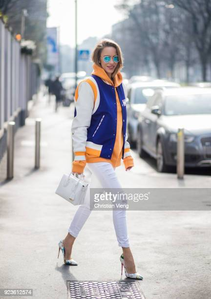 Alexandra Lapp wearing a college jacket in blue white and orange from MCM an orange hoodie from glamometer white destroyed jeans from Frame a white...