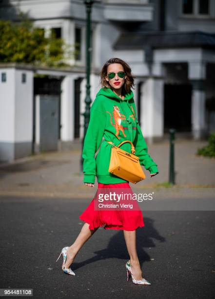 Alexandra Lapp wearing a green tiger print Gucci logo hoodie, a red pleated skirt by SET, a Hermes Birkin 30 bag in orange, Pigalle Follies pumps by...