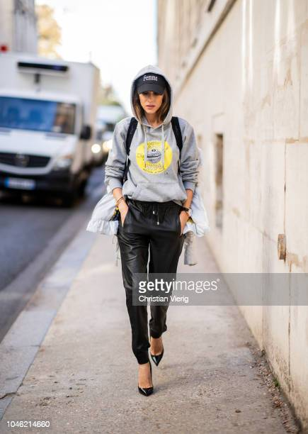 Alexandra Lapp wearing a light grey fitted down jacket with inner carriers by Airfield a handmade grey Hoodie with handpainted print by Wodka Ogurez...