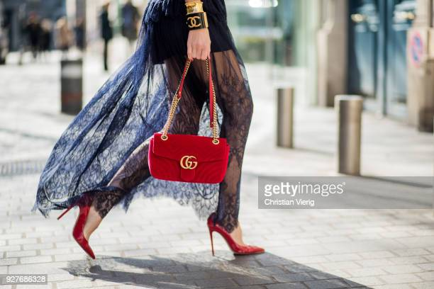 Alexandra Lapp wearing a long dark blue Self-Portrait lace dress, red patent Gianvito Rossi pumps, Chanel bracelet with golden CC sign, golden...