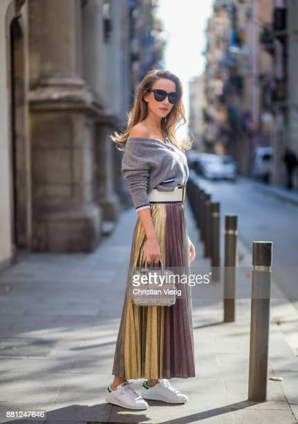 Alexandra Lapp wearing a long pleated metallic skirt with changing gold and red colors grey cashmere cardigan with pearl buttons and blue and white...