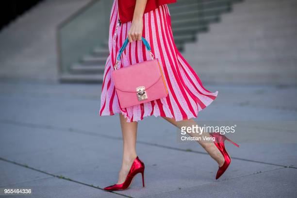Alexandra Lapp wearing a Marc Cain plisse skirt in multicolored pink a light pink longsleeve shirt by Marc Cain Sports a red training track jacket in...