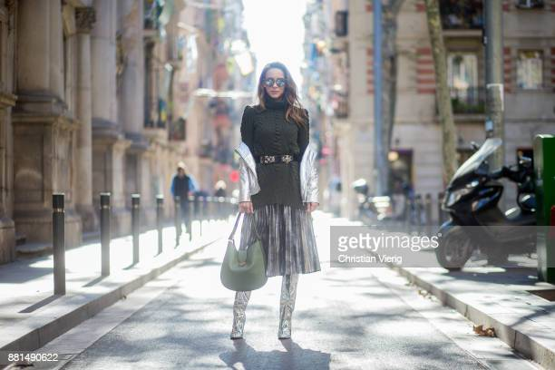 Alexandra Lapp wearing a pleated skirt in a washed out silver metallic and black style long knitted dark green Celine turtle neck pullover with cable...
