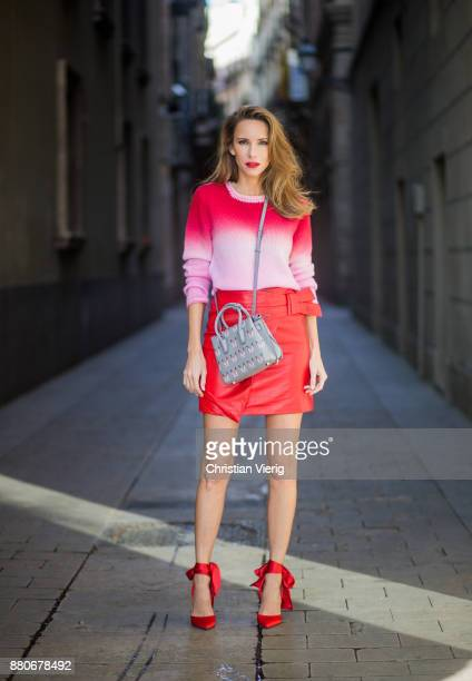 Alexandra Lapp wearing a red leather mini skirt with integrated belt around the waist from Set Fashion a batik cashmere pullover in pink and red from...