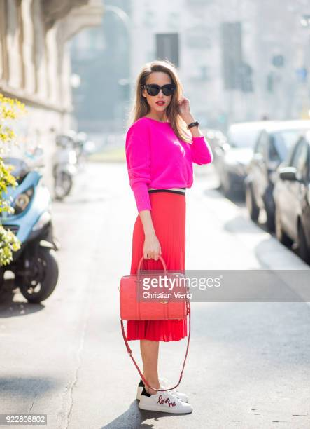 Alexandra Lapp wearing a red pleated skirt fro SET pink cashmere pullover from Jadicted sneakers from Steffen Schraut Audrey sunglasses in black from...