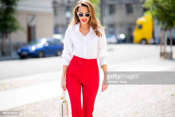 Alexandra Lapp wearing a red suit combination in bright red with high waist pants with an attached belt and a slim cut blazer with an integrated...