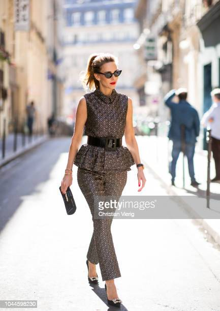 Alexandra Lapp wearing a ruffled top with a collar and no arms from No21 in a shiny bronze and silver pattern with matching slim cut pants black...