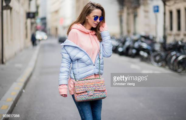 Alexandra Lapp wearing a short quilted grey jacket and a orange hoodie from Juvia dark blue jeans by AG Jeans high sandals from Sophia Webster with...