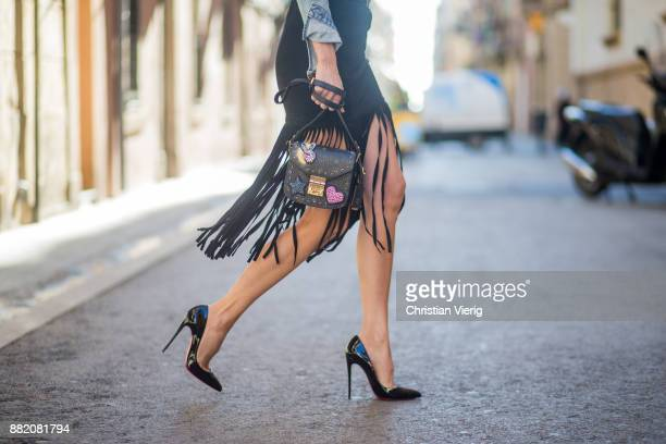 Alexandra Lapp wearing a suede leather fringe skirt in black from Set Fashion light blue vintage jeans jacket by Levis black lacquer waist belt by...