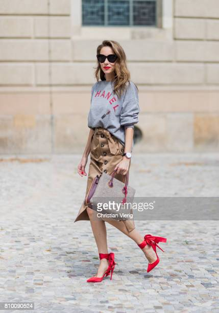 Alexandra Lapp wearing a vintage sweater from Chanel in grey melange, printed with Chanel red capital letters, a red lipstick and a powder box from...