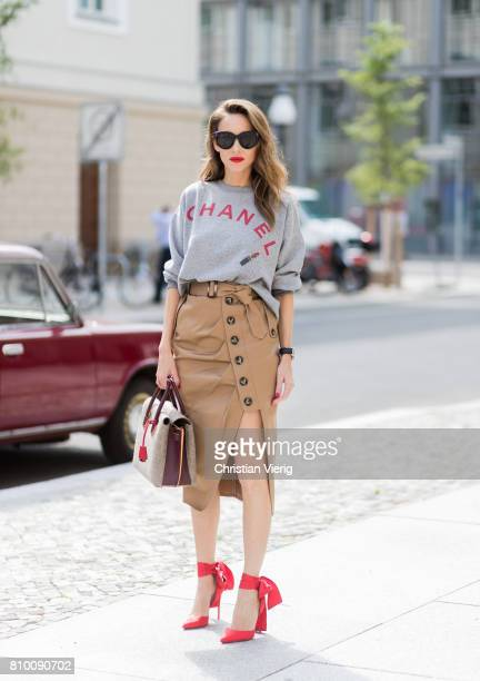 Alexandra Lapp wearing a vintage sweater from Chanel in grey melange printed with Chanel red capital letters a red lipstick and a powder box from...