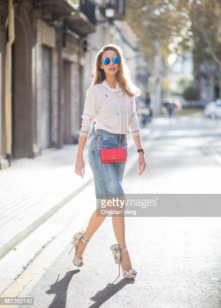 Alexandra Lapp wearing a white cashmere hoodie with colored flower applications from Heartbreaker high rise jeans skirt with slit Adriano Goldschmied...
