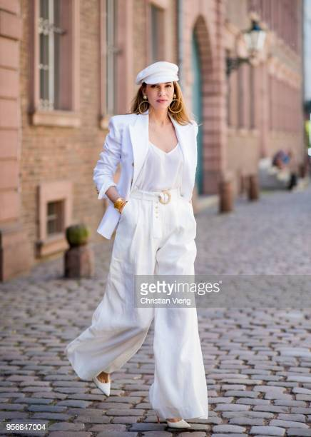 Alexandra Lapp wearing a white cotton blazer with gold buttons by Balmain linen Palazzo pants with a high waist belt in white by Zimmermann a white...