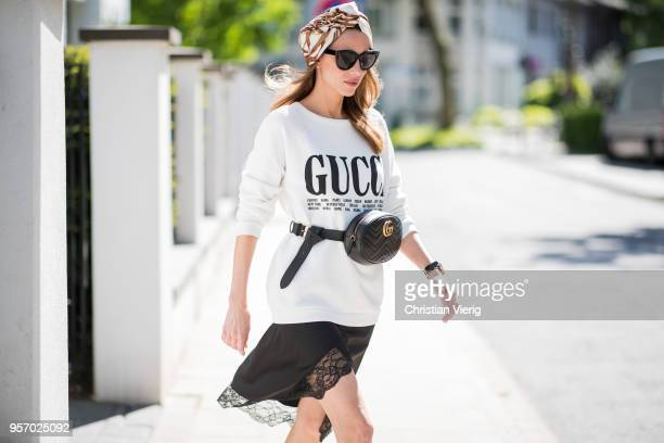 Alexandra Lapp wearing a white crewneck cotton sweatshirt by Gucci black double layered lace skirt by Zara the black GG Marmont matelasse belt bag in...