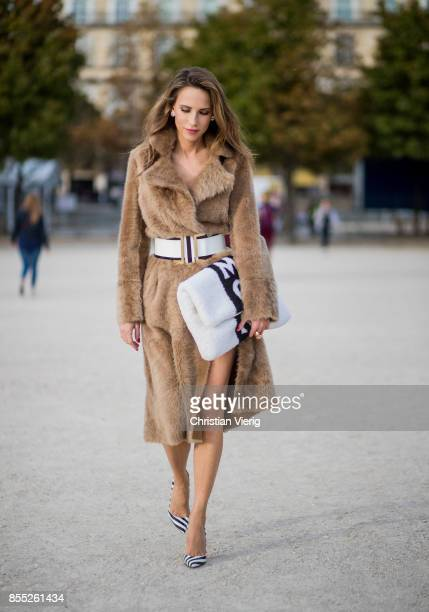 Alexandra Lapp wearing an oversized MCM Stark Pouch in Shearling Stripe a lambskin coat in light brown by Yves Salomon black and white big waistbelt...