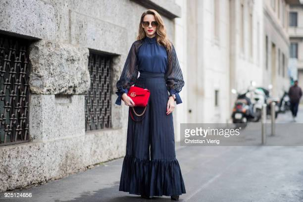 Alexandra Lapp wearing black flared pants and a matching blouse with transparent arms from Nobi Talai sunglasses from Maison Mavada and a red velvet...