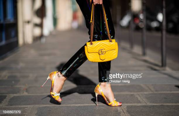 Alexandra Lapp wearing black zipped patent leather trousers from Balmain a yellow vneck knit jumper by Allude shiny black down jacket by Ahirain...