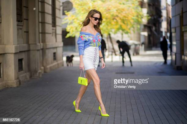 Alexandra Lapp wearing blue cashmere cardigan with stitched flower applications from Heartbreaker of shoulder style white leather skirt with silver...