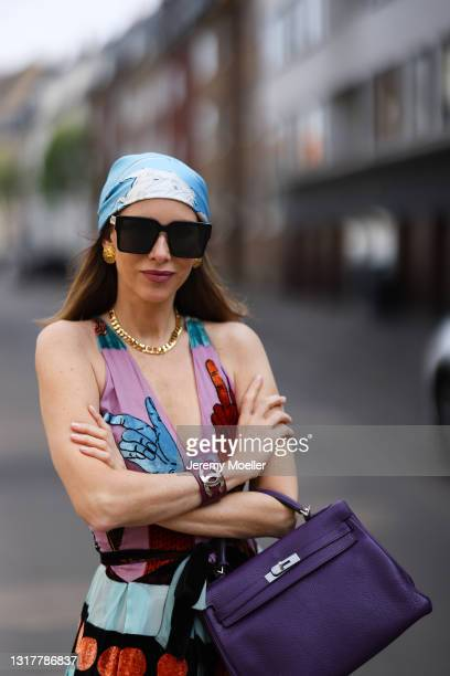 Alexandra Lapp wearing colorful Valentino dress, purple Hermès Kelly bag and blue Hermès scarf, gold Dior necklace and gold Chanel earring and black...