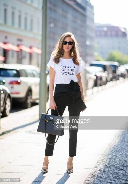 Alexandra Lapp wearing Cool Ambition Semi Loose Fit Pants in black from Dorothee Schumacher with a high waist white strong statement shirt saying...