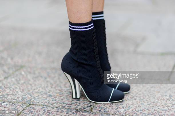 Alexandra Lapp wearing Fendi's SS '17 collection sockboots with a grey knit upper with a high sculptural heel a black silk chiffon mini dress with...