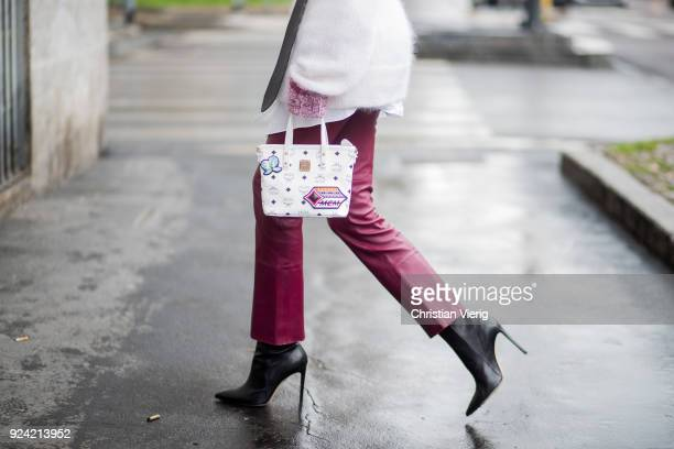 Alexandra Lapp wearing flared leather pants in bordeaux by Dorothee Schumacher an offwhite cotton pullover with a bordeaux colored neckline and a...