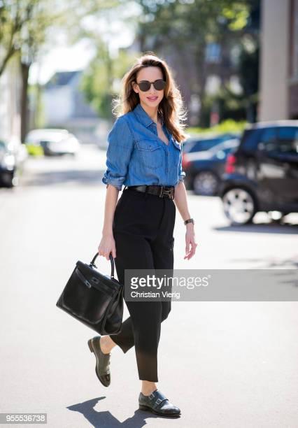 Alexandra Lapp wearing high waist black ankle cropped trousers by Zara a blue Steffen Schraut denim shirt a black vintage logo belt by Hermes the...