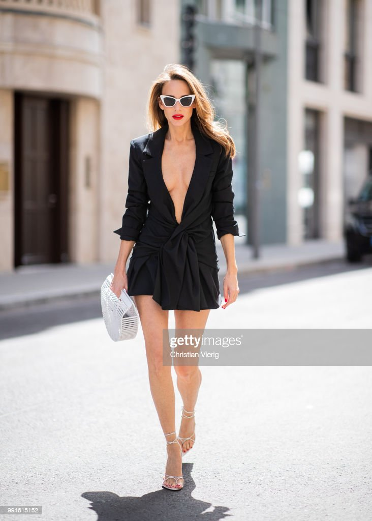 Alexandra Lapp wearing 'La veste Rafael' drapped black tailored dress jacket by Jacquemus, Inez sandals by Saint Laurent in Blanc Optique, Victoire Sunglasses in white by Saint Laurent and bag Gaias Ark in white by Cult Gaia during the Berlin Fashion Week July 2018 on July 6, 2018 in Berlin, Germany.