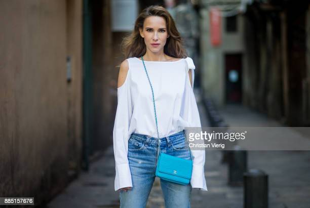Alexandra Lapp wearing white off-shoulder blouse, multicolored Sophia Webster sandals heels, vintage Levis from ReDone and Chanel purse bag with a...