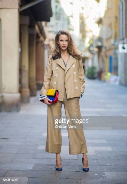 Alexandra Lapp wearing wide cut khaki pants from Steffen Schraut, khaki jacket with blue collar and blue and white strips on the bottom of the sleeve...