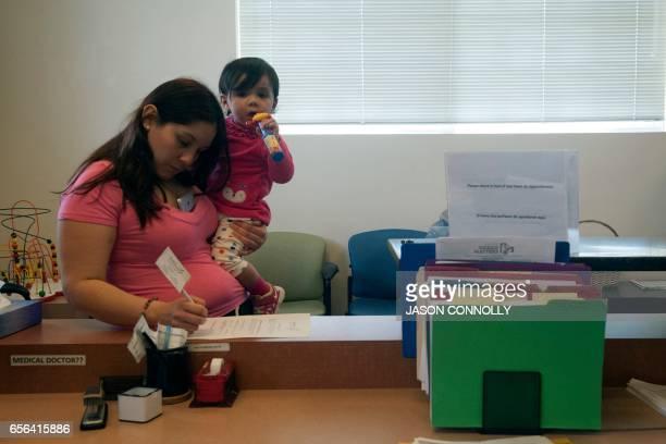 Alexandra Olivares fills out paperwork during a visit at Inner City Health Center in Denver Colorado on March 15 2017 Inner City Health Center was...