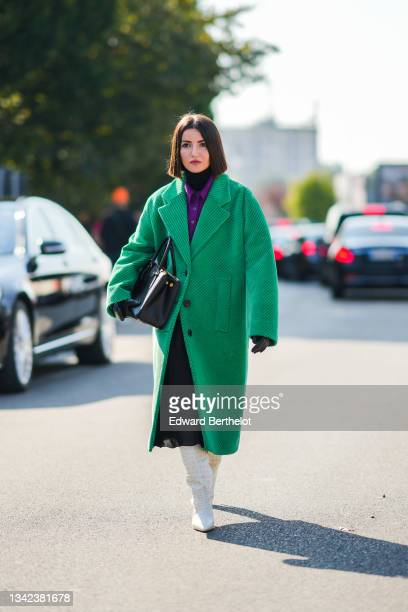 Alexandra Pereira wears a black turtleneck pullover, a neon purple wool polo shirt, a green ribbed velvet oversized long coat, a black shiny leather...