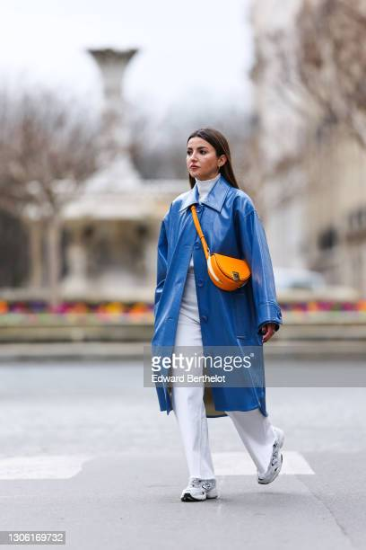 Alexandra Pereira wears a white turtleneck pullover / sweater from Zara, a blue long trench coat from Stand Studio, white flare denim jeans from...