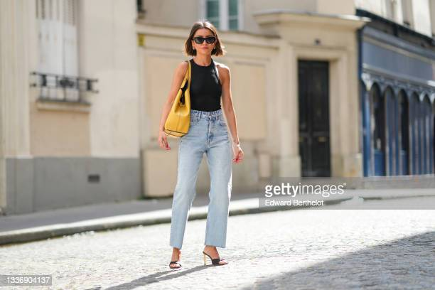 Alexandra Pereira wears black sunglasses, gold earrings, a black ribbed halter-neck cropped t-shirt, blue faded denim high waist ripped flared jeans...