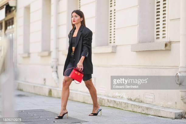 Alexandra Pereira wears gold earrings, a black shoulder off crop-top, an oversized long black blazer jacket from The Frankie Shop, a gold chain belt...