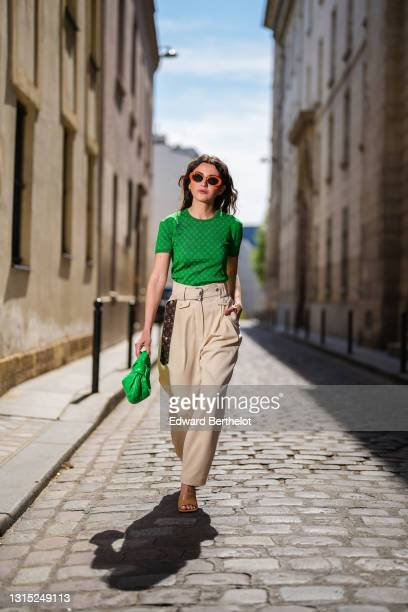 Alexandra Pereira wears orange sunglasses, a neon bold green Louis Vuitton t-shirt with printed monograms, neon bold green woven leather bag from...