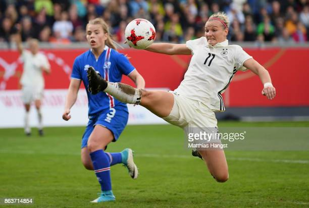 Alexandra Popp of Germany is challenged by Ingibjoerg Sigurdardottir of Iceland during the 2019 FIFA Women's World Championship Qualifier match...
