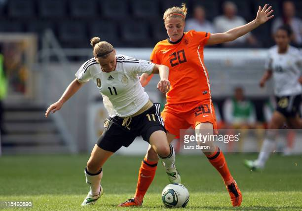 Alexandra Popp of Germany is challenged by Kirsten van de Ven of Netherlands during the Women's International friendly match between Germany and...