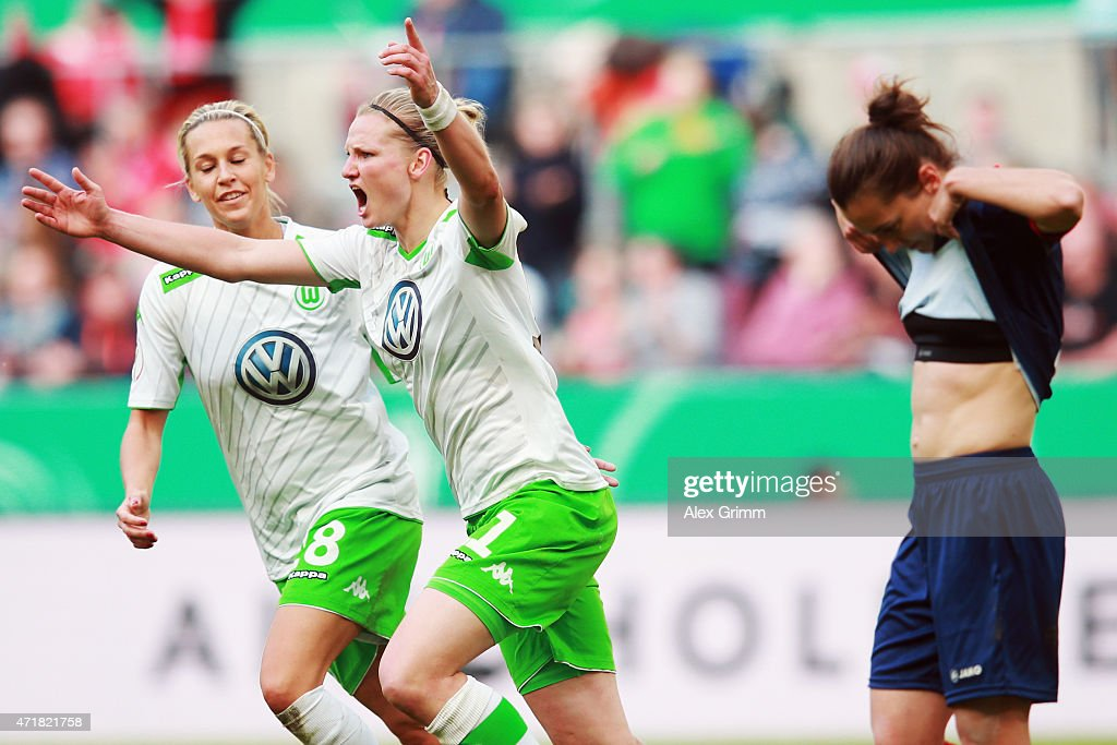 Alexandra Popp of Wolfsburg celebrates her team's third goal with team mate Lena Goessling as Lidija Kulis of Potsdam reacts during the Women's DFB Cup Final between Turbine Potsdam and VfL Wolfsburg at RheinEnergieStadion on May 1, 2015 in Cologne, Germany.