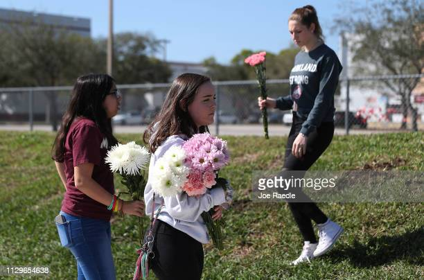 Alexandra Rozenblat Lily Lahaye and Melena Plough all juniors at Marjory Stoneman Douglas High School visit a memorial setup next to the school in...