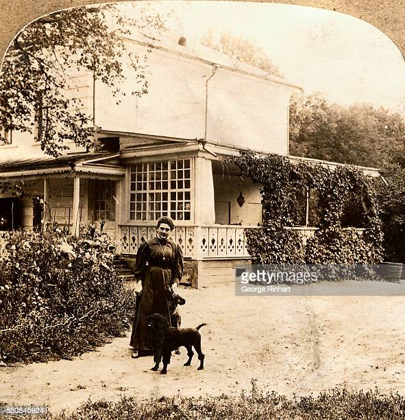 Alexandra Tolstoy is shown standing outdoors with a black dog