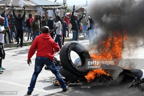 Alexandra township residents burn tires in the middle of the street as they clash with the Johannesburg Metro Police on April 3 2019 in Johannesburg...