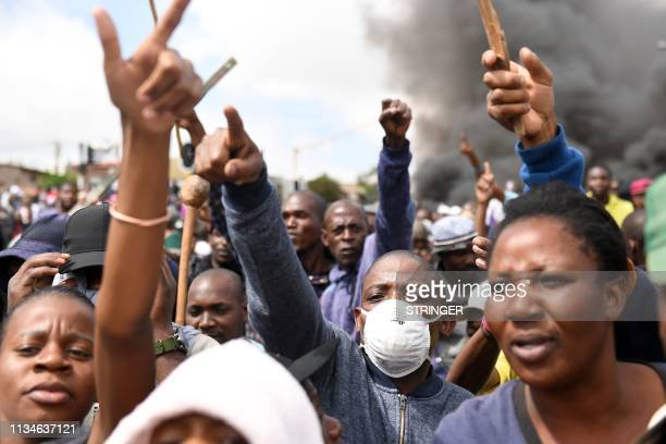 Alexandra township residents gesture and chant slogans as they clash with the Johannesburg Metro Police on April 3 2019 in Johannesburg South Africa...