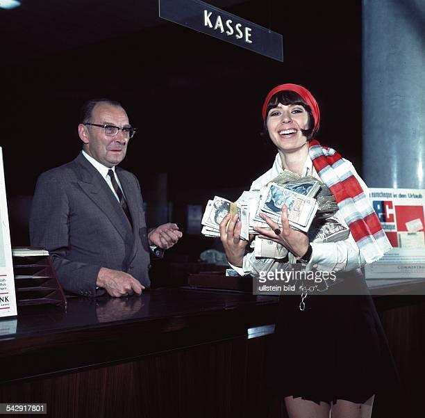 Alexandraeigentlich Alexandra Nefedov Treitz*Sängerin steht an einer Kasse und hat die Arme voller Geldscheine undatiert