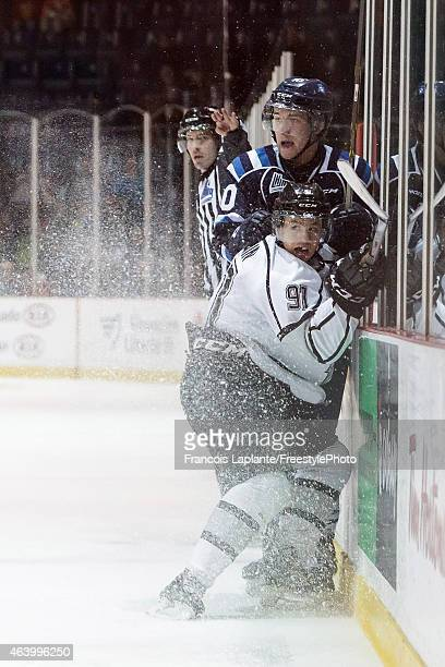 Alexandre Alain of the Gatineau Olympiques checks into the boards Jesse Lussier of the Chicoutimi Sagueneens on February 20, 2015 at Robert Guertin...